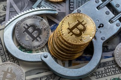 03_Stack-of-bitcoins-and-metal-handcuffs-on-banknotes.jpg